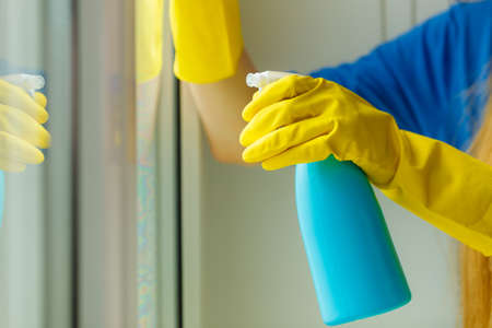 Female hand in yellow gloves cleaning window with blue rag and spray detergent. Spring cleanup, housework concept