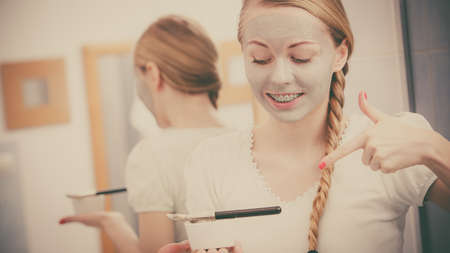 woman mirror: Skincare. Blonde smiling woman in bathroom gray clay mask on her face pointing with finger on bowl with mud. Young lady taking care of skin. Spa beauty wellness. Stock Photo