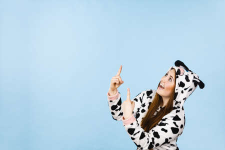 Happy teenage girl in funny nightclothes, pajamas cartoon style pointing up with positive surprised face expression, studio shot on blue. Advertisement concept