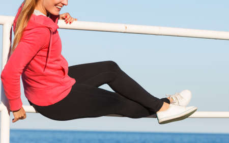 Outdoor, dangerous play, freedom and sport concept. Woman in sports suit sitting, relaxing after workout on handrail next to sea. Stock Photo