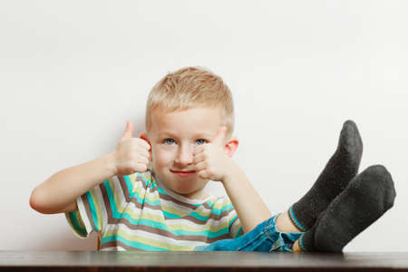 Childhood, kids imagination and gestures concept. Little young boy playing having fun, showing thumb up gesture