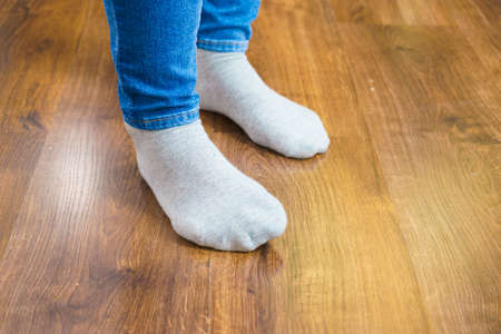 Woman feet wearing white socks and jeans trousers standing on wooden floor.