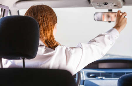 Young man wearing white shirt having long hair, driving car setting mirror inside to see better whats behind auto