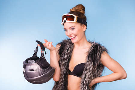winter fashion: Winter sport activity concept. Atractive smiling girl wearing black bra, ski goggles and furry waistcoat holding helmet, blue background studio shot.