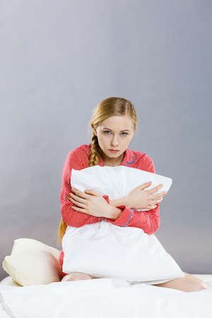 Mental health depression insomia concept. Sad depressive young woman teen blonde girl wearing red pajamas sitting on bed embracing pillow, on grey wall background Banque d'images