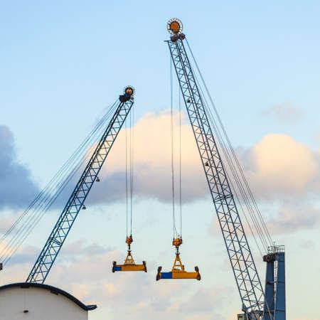 Huge industrial objects concept. Big construction machines in shipyard, sky in background.