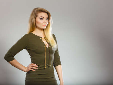 Fashionable outfit ideas, trendy clothes concept. Attractive blonde woman wearing tight dark green khaki dress