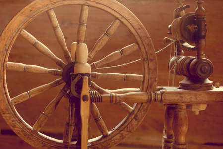 Traditional devices, vintage tailoring equipment concept. Old fashioned wooden distaff, spindle, spinning wheel
