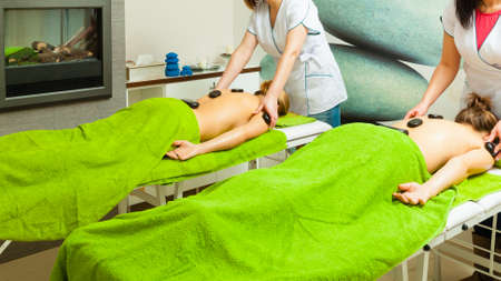 Spa relaxation, healthy pleasure concept. Two women lying on stomach having massage with hot rocks stones in beautician Stock Photo