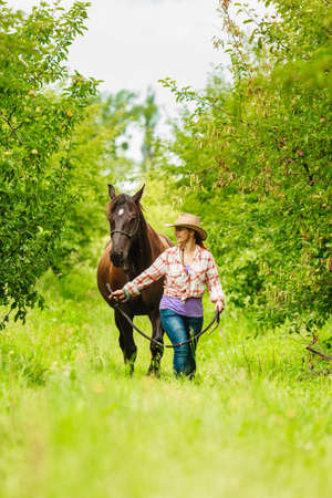 Actieve westerse cowgirl vrouw in hoed lopen met paard. Amerikaans meisje in plattelandsboerderij. Stockfoto