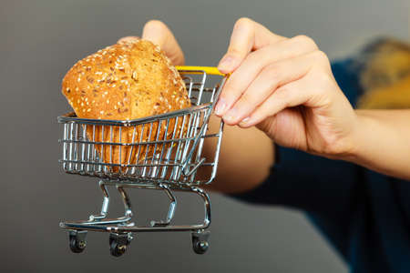 Buying gluten food products concept. Woman hand holding shopping cart trolley with small piece of bread
