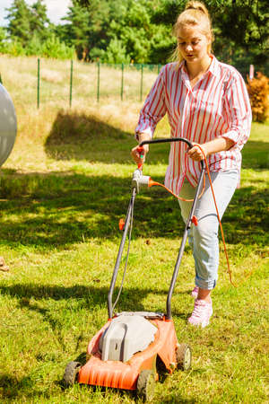 Gardening. Female person mowing green lawn with lawnmower in sunny day.