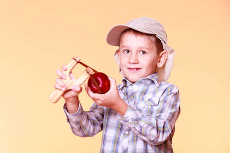 Nature and free time prankster little boy. Child have fun with  wooden sling shot and fruit hold apple. Stock Photo