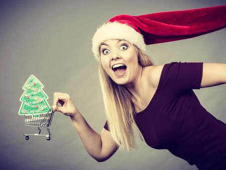 Xmas, seasonal sales, winter celebration concept. Happy woman wearing Santa helper hat holding shopping basket cart with little christmas tree inside running for sale.
