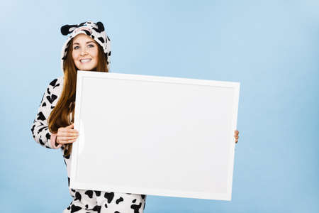 Smiling teenage girl in funny nightclothes, pajamas cartoon style with blank empty banner board. Advertisement copyspace.