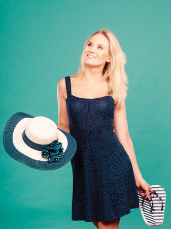 flip flops: Summer trendy fashionable outfit ideas concept. Woman wearing short navy dress holding sun hat and flip flops Stock Photo