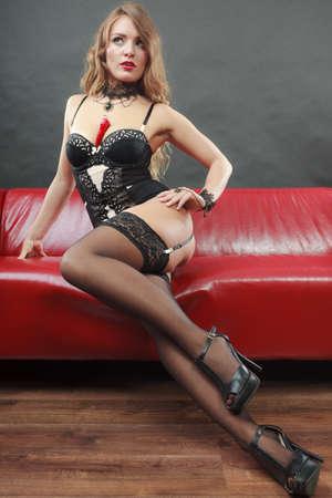 Sensuele verleidelijke aantrekkelijke vrouw in lingerie die en op rode bank met Spaanse peperspeper stellen stellen op borst, lange benen Stockfoto