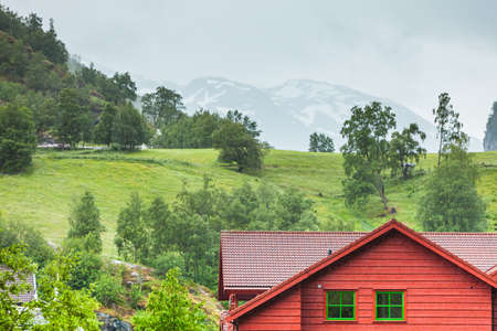 Wooden cottage cabin in the valley. Green summer misty mountains in the background. Foggy rainy weather. Norway. Stock Photo