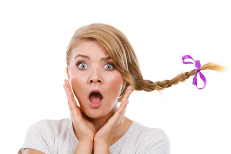 terrified woman: Emotions expressions, fooling around concept. Astonished teenage girl in blonde braid windblown hair making funny, shocked face. Stock Photo