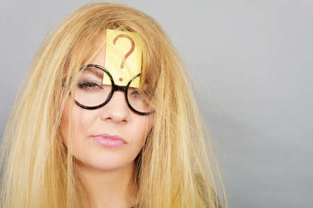 Mental effort, finding problem solution face expression concept. Tired crazy woman wearing nerd geek eyeglasses exhausted after intensive thinking having question mark on her forehead and messy hair