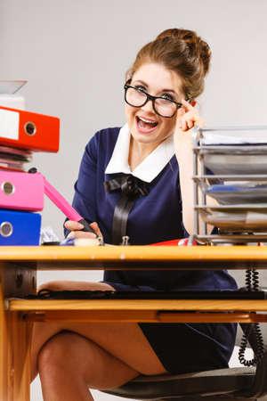 Happy business woman feeling energetic sitting working at desk full off documents in binders. Zdjęcie Seryjne