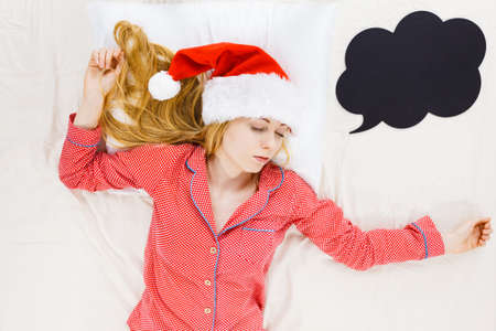 Sleeping woman waiting for Christmas season wearing pajamas and Santa Claus hat lying in bed dreaming about celebrating holiday, black speech bubble ballon next to her.