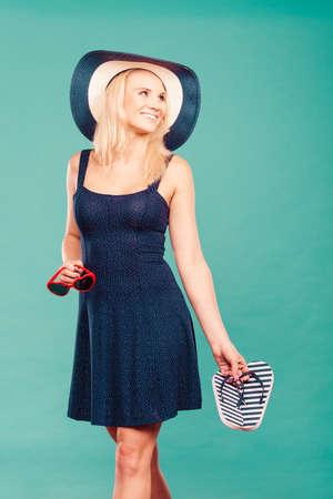 flip flops: Summer trendy fashionable outfit ideas concept. Woman wearing short navy dress sun hat holding flip flops and sunglasses.
