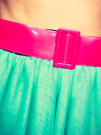 Woman fahion, accessories, clothing concept. Close up of pink belt on blue, turquoise tulle skirt