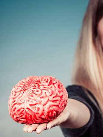 Woman hand holding brain. Having something on mind, thinking of solution idea concept. Stock Photo