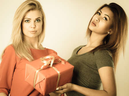 Occasions gifts people concept. Beautiful women blonde caucasian girl and mulatto with red gift box, toned image Stock Photo