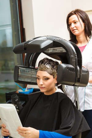 dryer: Haircare, relaxation and hairstyling concept. Woman sitting in black cape getting her hair dried under machine