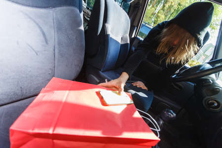 도난 방지 시스템 문제 개념. 스마트 폰 및 빨간색 쇼핑 가방을 훔치는 자동차에 침입 검은 옷을 입고 강도 도둑 남자