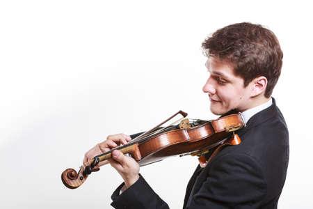 音楽のパッション、ホビーコンセプト若い男の人は優雅に木製のバイオリンで遊んで服を着ました。白い背景のスタジオショット
