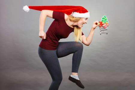 Xmas, seizoensgebonden verkoop, winterfeest concept. Gelukkige vrouw die Santa Claus-helperhoed draagt die het winkelen mandkarretje met kleine Kerstmisboom en giften binnen het runnen voor verkoop houdt. Stockfoto