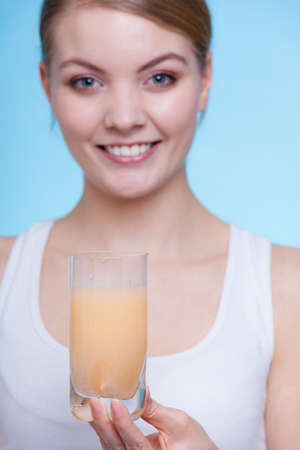 Vitamins, health, medicines. Woman holding glass with orange flavored vitamin mineral supplement effervescent tablet dissolved in water. Studio shot on blue background