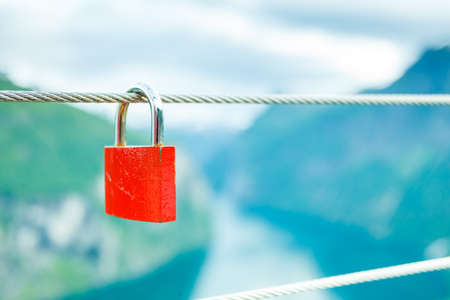 Tourism vacation and travel. Red love lock padlock on bridge and mountains, view over magical Geirangerfjorden from Flydalsjuvet viewpoint, Norway Scandinavia.