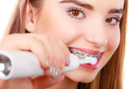 Dentist and orthodontist concept. Young woman smiling cleaning and brushing teeth with blue braces using toothbrush