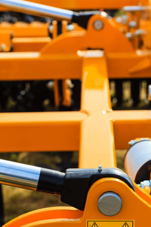 Industrial detailed pneumatic, hydraulic machinery concept. Pump made of steel on orange machine closeup.