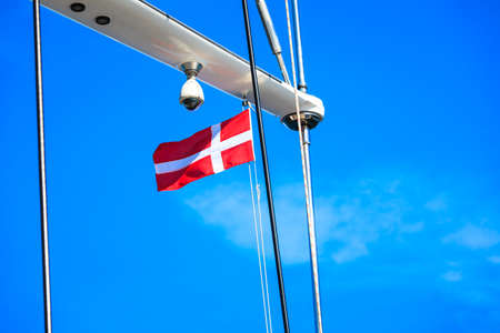 Denmark flag on ship sail boat mast with blue sky in background