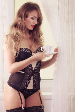 Sensual seductive attractive woman in lingerie holding cup by window with curtain at home. Stock Photo