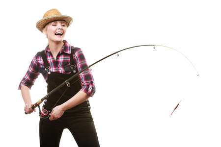 Spinning equipment, angling, cheerful fisherwoman concept. Happy woman in sun hat holding fishing rod, having fun while hunting for fish
