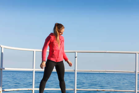 Outdoor relax, sport, fintess concept. Woman in sports suit standing on dyke next to sea resting after active workout.