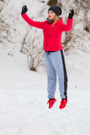 Outdoor sport exercising, sporty outfit ideas. Woman wearing warm sportswear training exercising outside during winter, jumping out of joy.