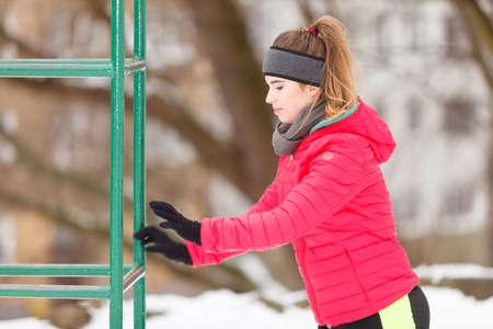 Workout in public park. Woman wearing warm sportswear urban street training exercising outside during winter.