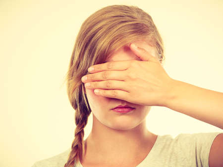 bashful: Anxiety, bullying at school concept. Shy teenage girl covering her face with hands. Stock Photo