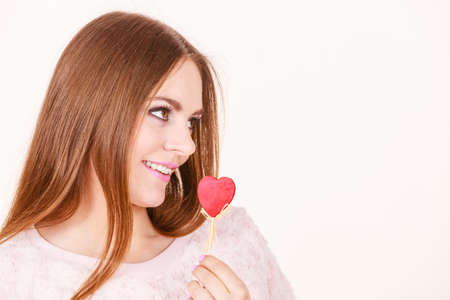 Romantic gestures, valentines gifts ideas concept. Happy flirty woman holding red wooden heart on stick.