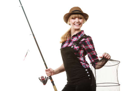 dungarees: Spinning, angling, cheerful fisherwoman concept. Happy woman in sun hat holding fishing rod and keepnet having fun.