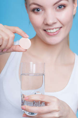 Vitamins, health, medicines. Woman holding glass with water and vitamin mineral supplement effervescent tablet. Studio shot on blue background