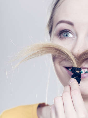 Woman making moustache out of braided blonde hair. Haircare, hairstyling having fun, on grey Stock Photo