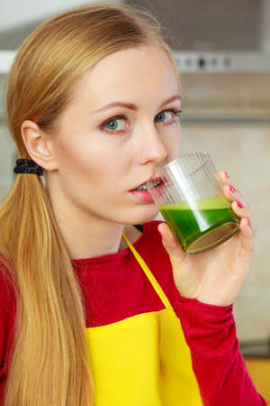 medula: Drinks good for health, diet breakfast concept. Young woman in kitchen holding green healthy vegetable smoothie juice glass